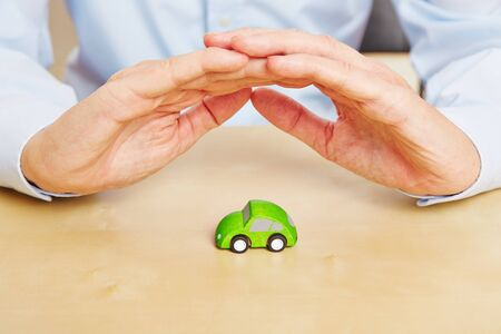 locomotion: Two hands protecting a small green car as concept for car insurance