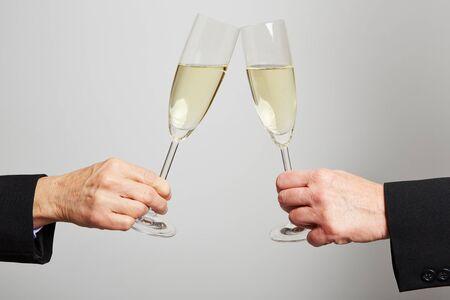 clinking: Dos manos de edad bebiendo champ�n para la celebraci�n Foto de archivo