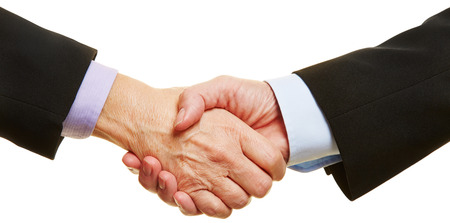 Panorama of business handshake with two elderly hands photo