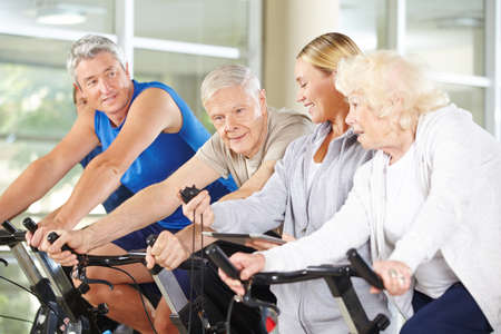 computer clubs: Trainer showing stopwatch to senior group on spinning bikes in gym