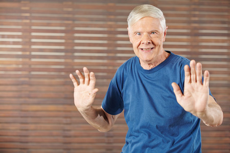 Old man doing gymnastics in fitness center and moving his hands photo