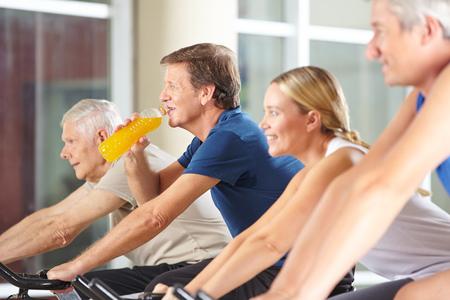 or thirsty: Hombre sediento que bebe el zumo de naranja en el gimnasio en bicicleta de spinning
