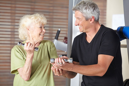 muscle formation: Fitness instructor helping smiling senior woman in rehab gym