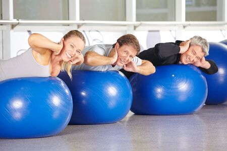 back training: Happy group of senior people on gym balls doing back training in fitness center