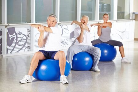muscle formation: Group of senior people stretching in gym and sitting on exercise balls