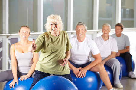 Old smiling woman in gym holding her thumbs up in fitness class Stock Photo