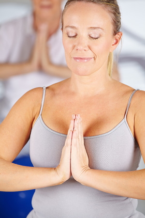 Woman doing relaxation exercise in gym in a yoga class photo