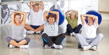 senior fitness: Senior group stretching in fitness center before doing back training