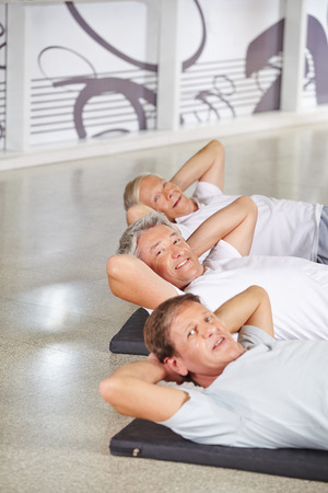 Men exercise: Happy group of senior people doing crunches in a gym