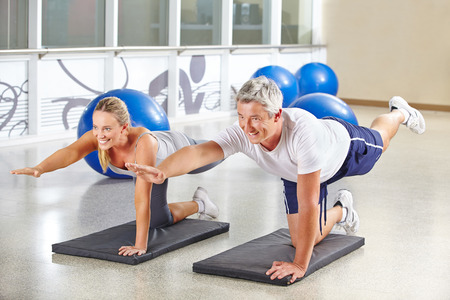 Man and woman doing gymnastics together in a fitness center
