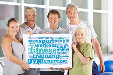 senior fitness: Senior people group holding fitness tag cloud in gym on cardboard sign Stock Photo