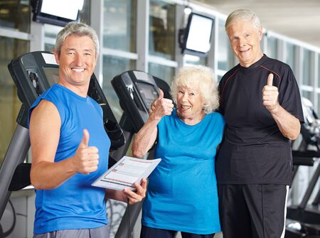 senior fitness: Happy senior couple in gym holding thumbs up with fitness trainer