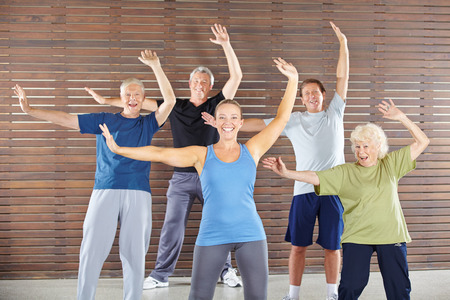 an elderly person: Group of happy seniors dancing and exercising in gym class