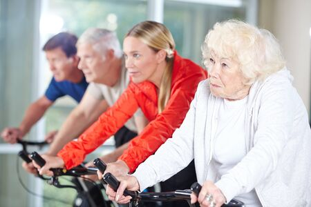 senior care: Senior group together in a spinning class in rehab care center Stock Photo