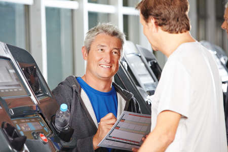 muscle formation: Trainer in fitness center advising senior man on a treadmill