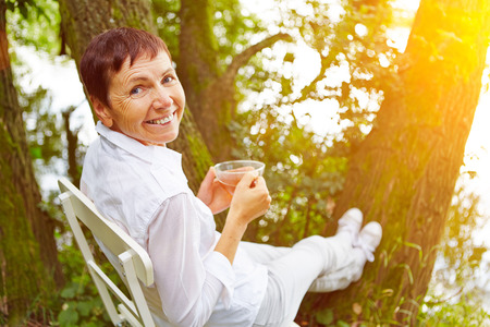 senior citizens: Relaxed senior woman taking a break with cup of tea in her garden Stock Photo