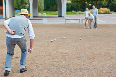 retirement home: Senior group playing boule together in a city in front of a retirement hime Stock Photo