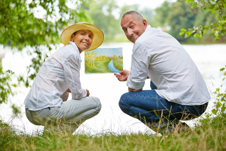 art therapy: Senior people learning to paint in art class in nature on a lake