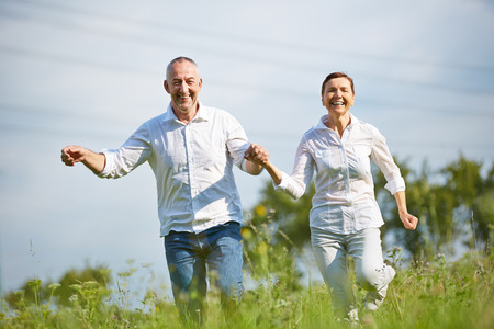 Happy senior couple running over meadow in summer