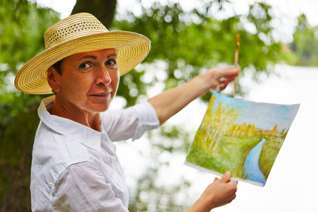 art therapy: Senior woman painting a watercolor picture in nature in summer Stock Photo