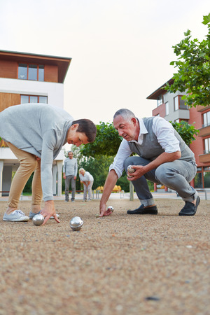 pick up: Senior group playing boule together outside in a city