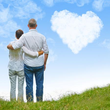 familia abrazo: Pareja de ancianos en una colina que mira a una nube corazón blanco en un cielo azul