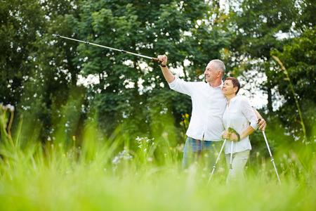 Senior Paar Wandern und Menschen, die auf der Strecke mit Gehstock Standard-Bild - 36835749