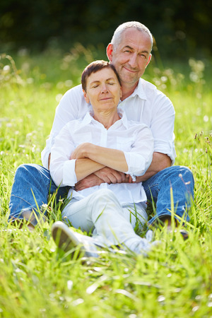 lean out: Happy senior couple sitting relaxed together in nature in summer Stock Photo