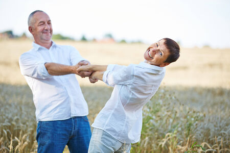 hand movements: Smiling senior couple dancing in summer in a wheat field Stock Photo