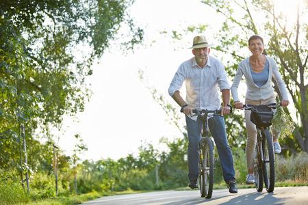 여름에 자전거 경로에 자전거를 타고 행복 한 고위 커플 스톡 콘텐츠