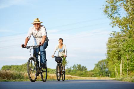 Senior paar paardrijden fietsen door de zomer landschap op een weg Stockfoto