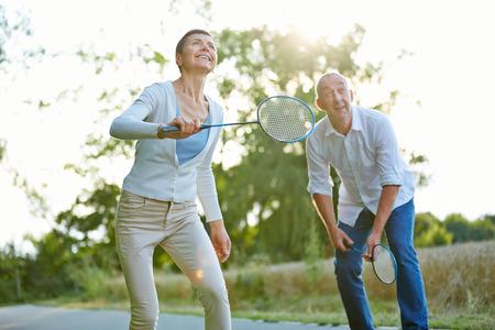 Senior paar spelen badminton in de zomer in de natuur