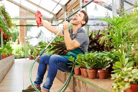 Happy gardener singing in water hose in a greenhouse of a nursery shop photo