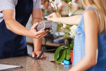 stores: Mobiel betalen met smartphone bij de kassa in de kwekerij winkel Stockfoto