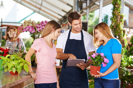 garden staff: Gardener in a nursery shop giving advice to two female customers
