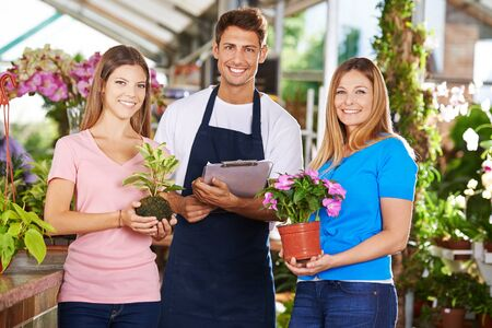 floristry: Happy gardener team group in nursery shop with plants and flowers