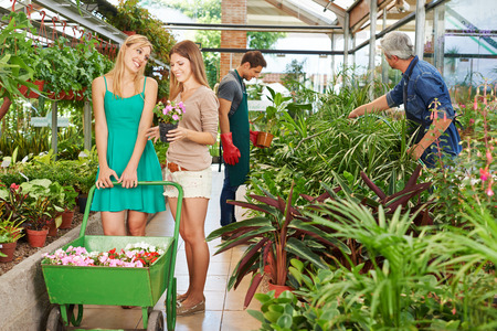 garden staff: Two happy women buying flowers together in a nursery shop Stock Photo