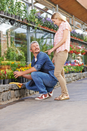garden staff: Smiling woman talking to a gardener in a nursery shop Stock Photo