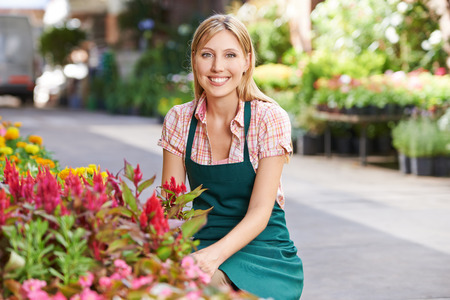 garden staff: Smiling young woman working as gardener in a nursery shop