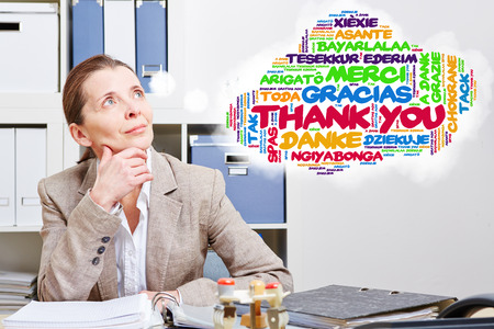 many thanks: Old woman thinking about thank you in many languages in her office
