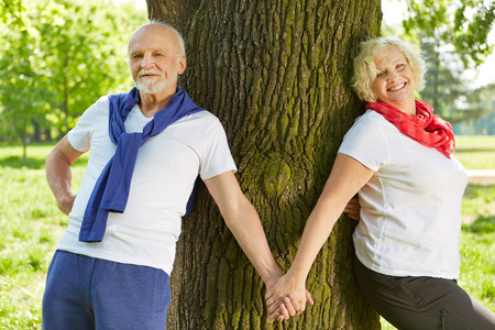 lean on hands: Happy senior couple holding hands in nature leaning on a tree