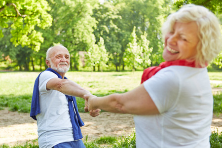 vital: Happy senior couple dancing together in nature in summer