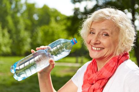 Smiling senior woman drinking fresh water in summer