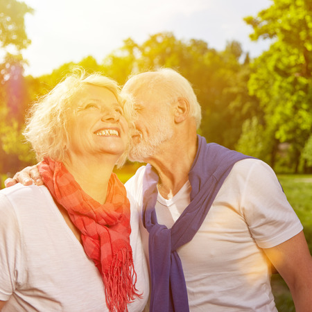 Old man kissing happy senior woman on cheek in summer