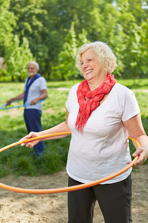 senior citizens: Two happy senior people doing sports with hoop in nature