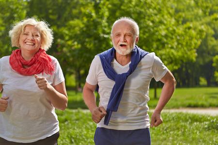 2 つの幸せなシニア人夏の公園でジョギング