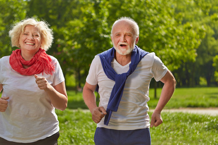 Two happy senior people jogging in a park in summer Stock Photo