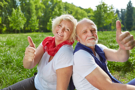 Happy old senior couple holding thumbs up in nature