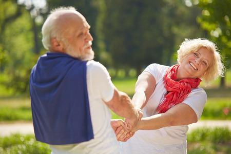 Oude man en senior vrouw dansen in een tuin in de zomer Stockfoto