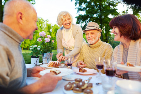 senior old: Happy seniors at birthday party sitting with cake in the garden Stock Photo